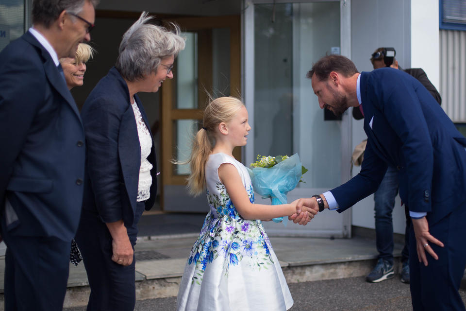 Blomsterpiken Hedda Skau tar imot Kronprinsen foran Anne Lycke, Arve Mjelva og Toril Tømte.